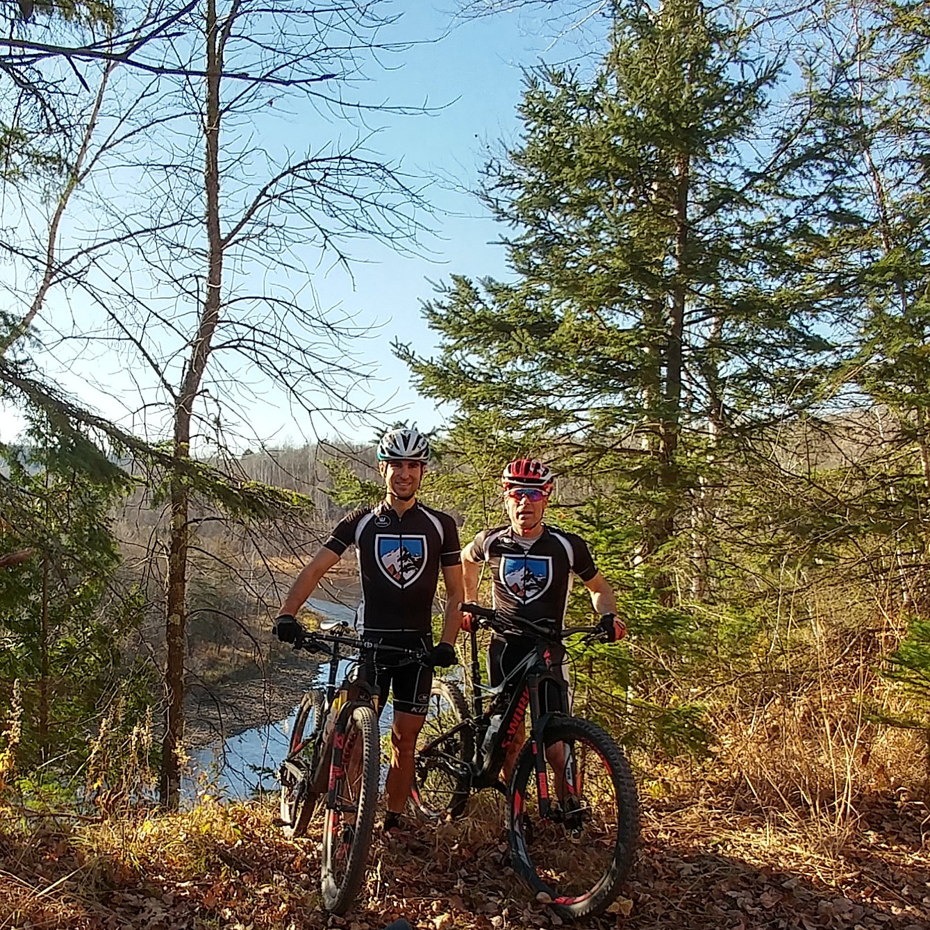 Two men from KUHL Bike Team stand next to their bycicles in a fall forest trail