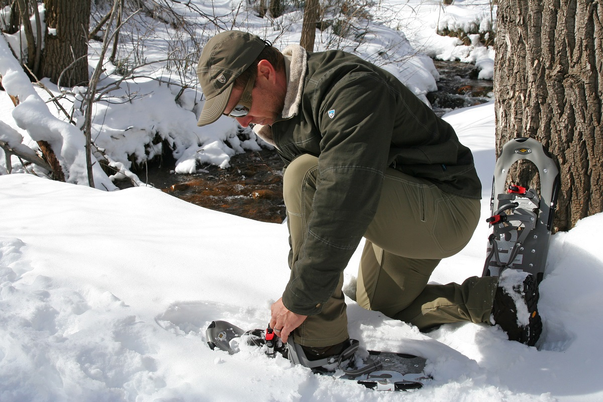 A man putting on a snowshoe on a snowy trail.