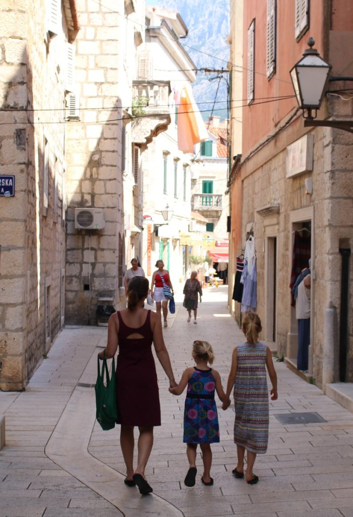 Mom and two daughters walk holding hands in Croatia.
