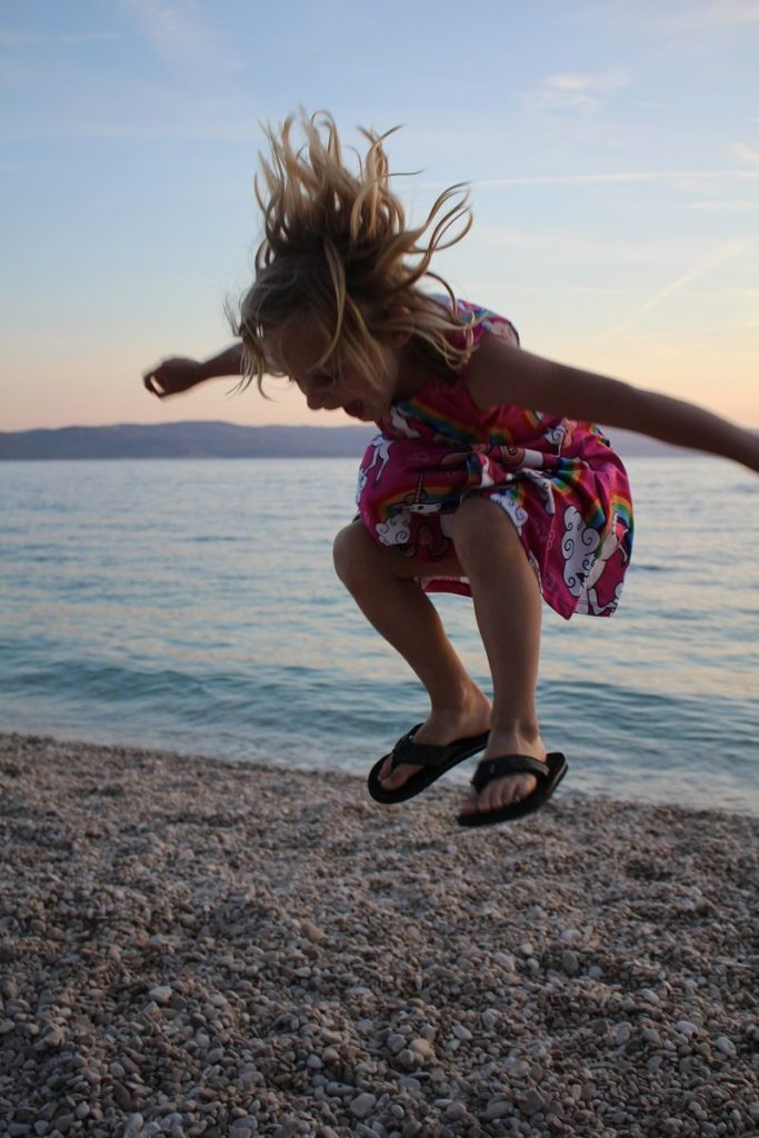 Blonde girl jumping on a pebble beach in Croatia.