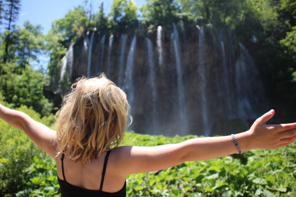 A blonde girl looking at a waterfall in Croatia.