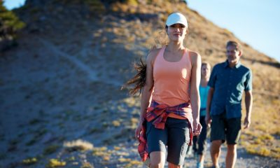 Two women and a man hiking down a rocky hill.