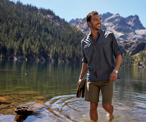 A man walking in a lake holding his flip-flops, mountain and forest in the background