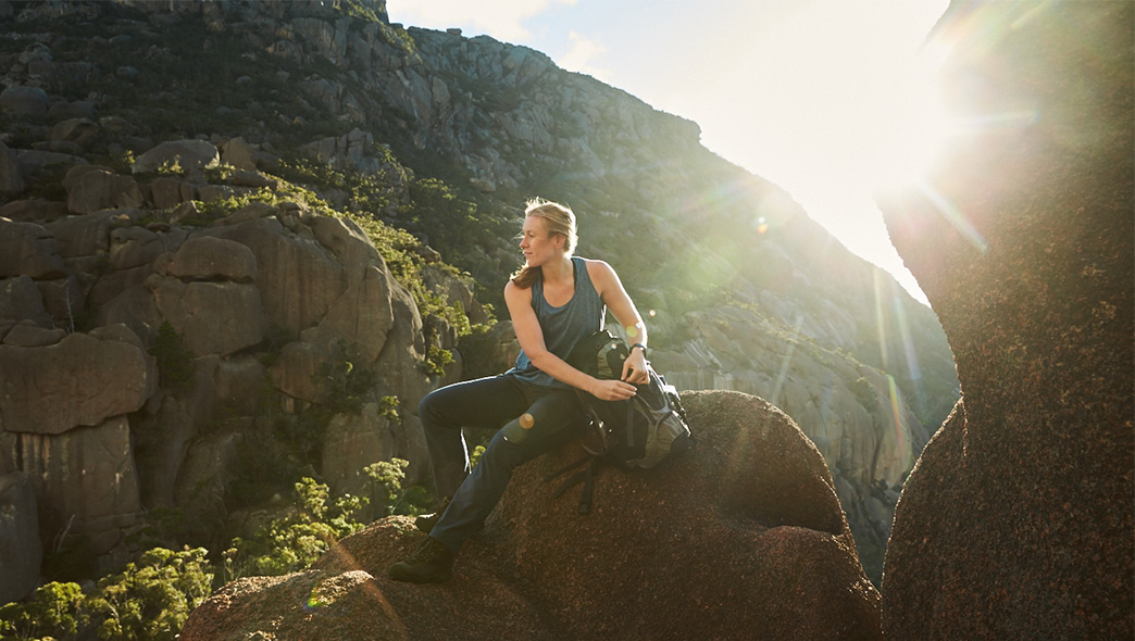 A lady wearing sun protective clothing is resting on a rock