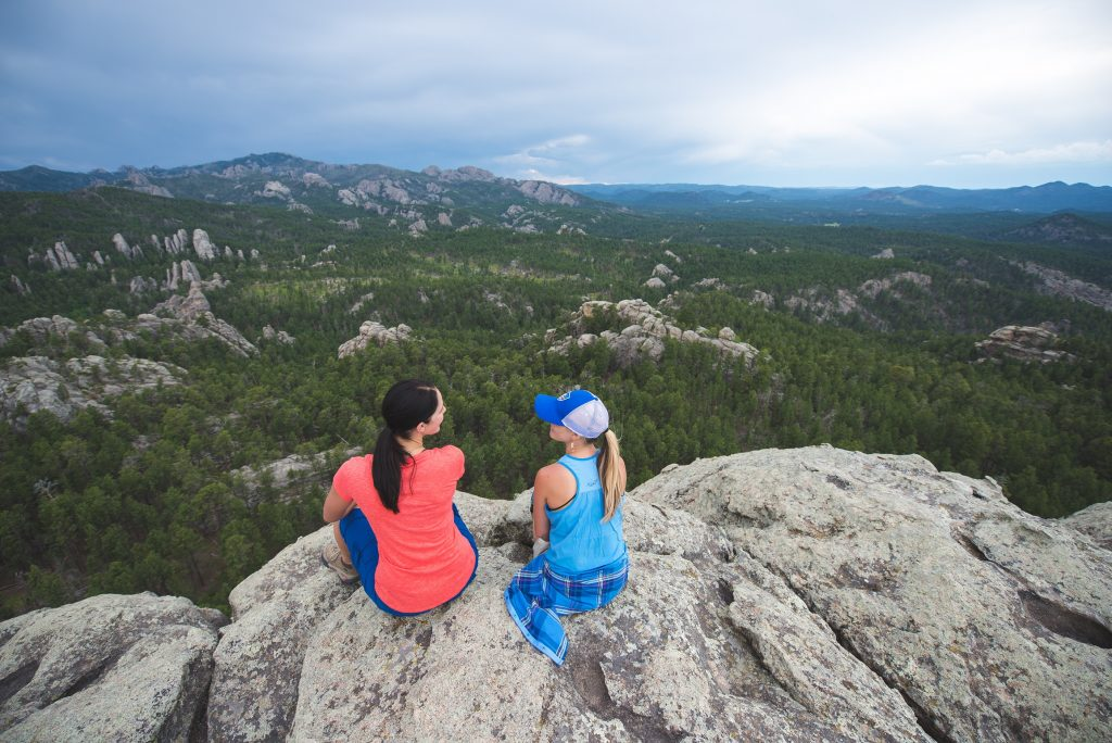 Two women sitting on a rock overlooking a forest, dressed in KUHL clothing.