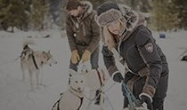 A man and a woman dressed in KÜHL outdoor clothing for snow and winter, putting a leash on one of the dogs.
