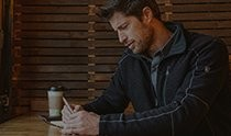 A man writing down notes and drinking coffee next to a wooden wall, wearing men's hiking clothing and KÜHL outerwear.