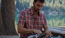 A man looking at his backpack after hiking in the forest dressed in KÜHL men's short sleeve shirt