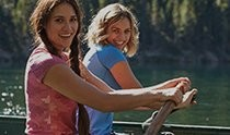 Two girls rowing on a lake, dressed in KÜHL women's short sleeve shirt