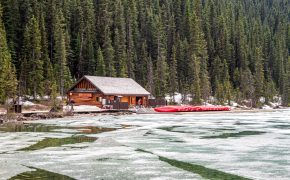 Brown wooden house surrounded by pine trees, kayaks and iced lake