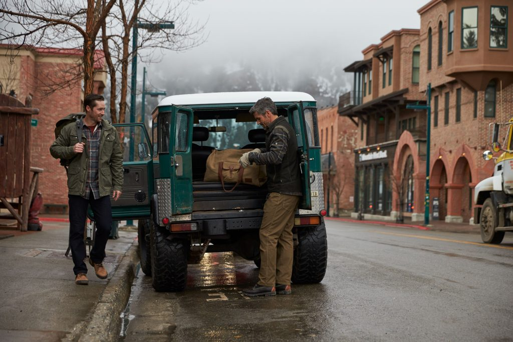 Two men standing next to a teal truck in a snowy small town.
