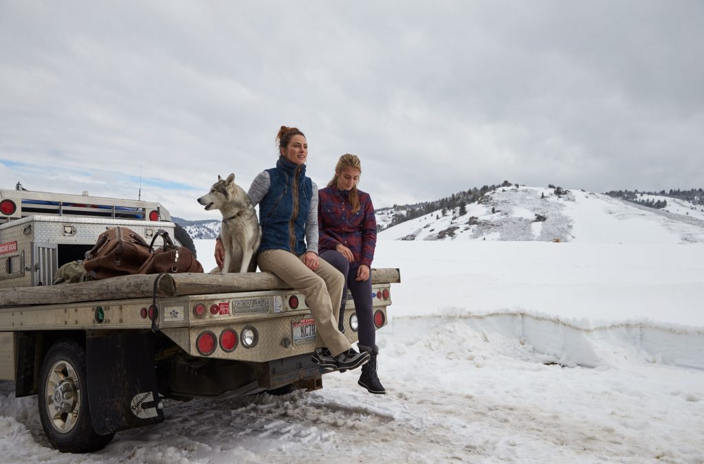 Two women sitting on the back of a truck, petting a dog in a winter scenery.