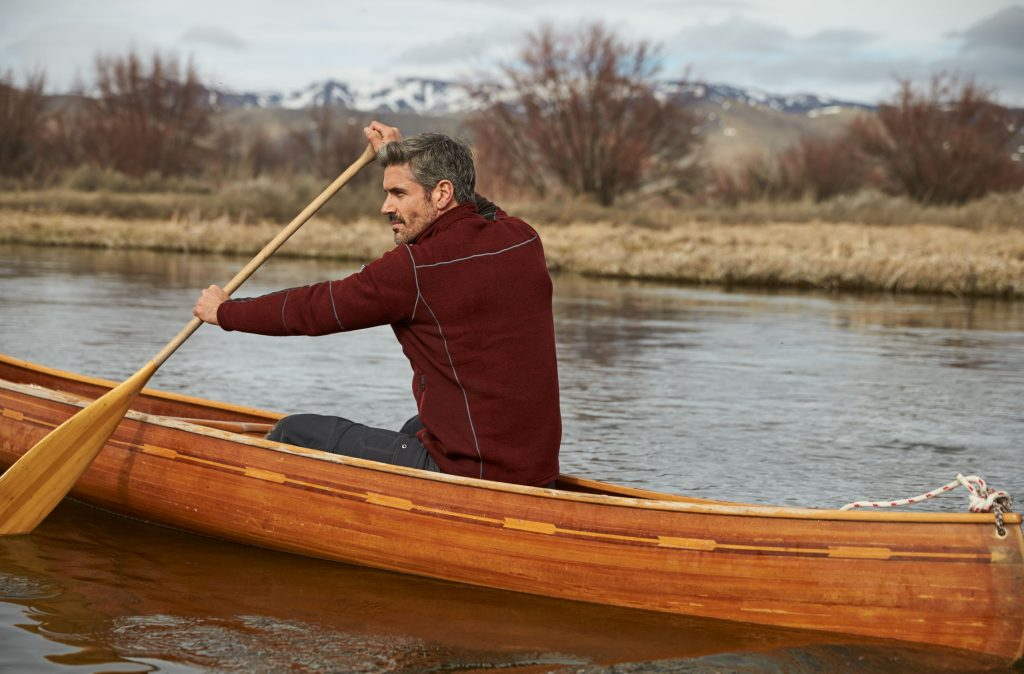 A man dressed in mens outerwear paddling in a kayak during winter