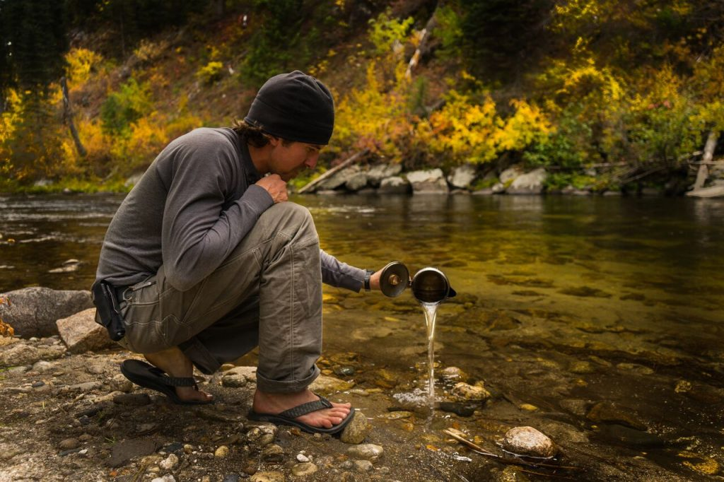 A man wearing KUHL Clothing men's hiking pants and men's long sleeve shirt pouring water in a creek.