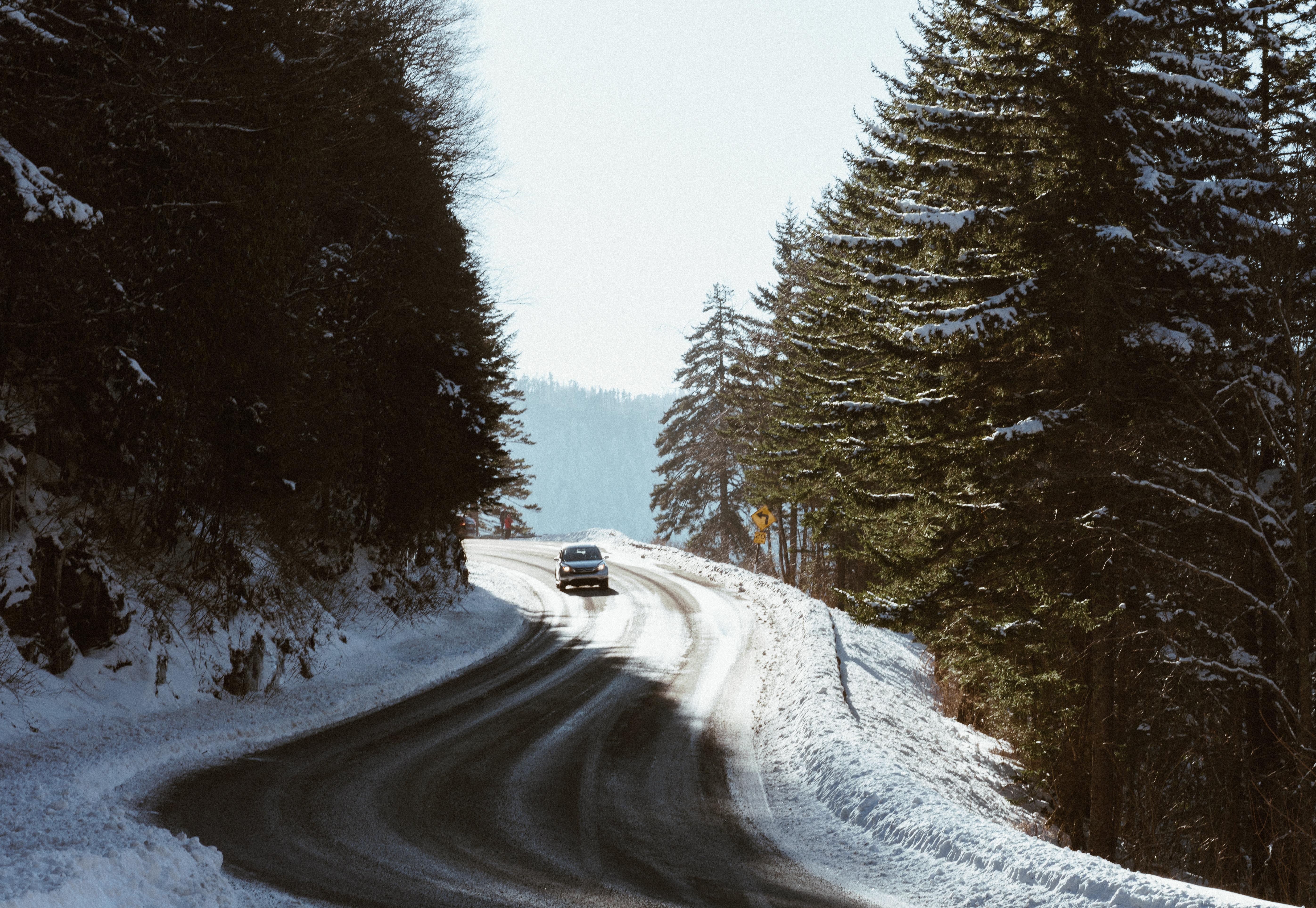 Car on snowy road surrounded by tall trees
