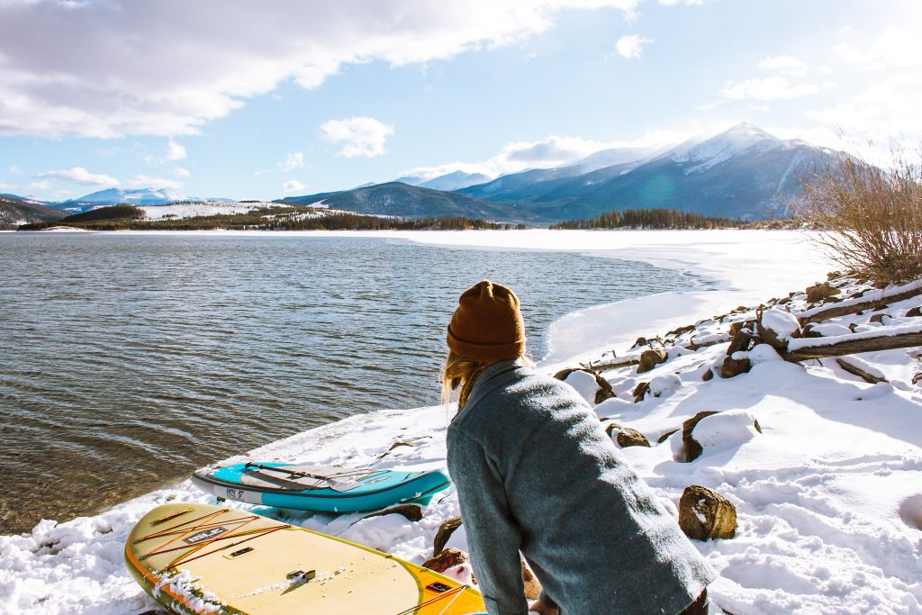 A woman pushing her paddling board in a river from a snowy shore.
