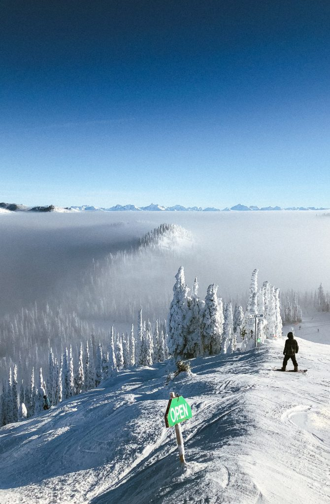 An open skiing slope with snow covered trees and fog in the distance during daytime.