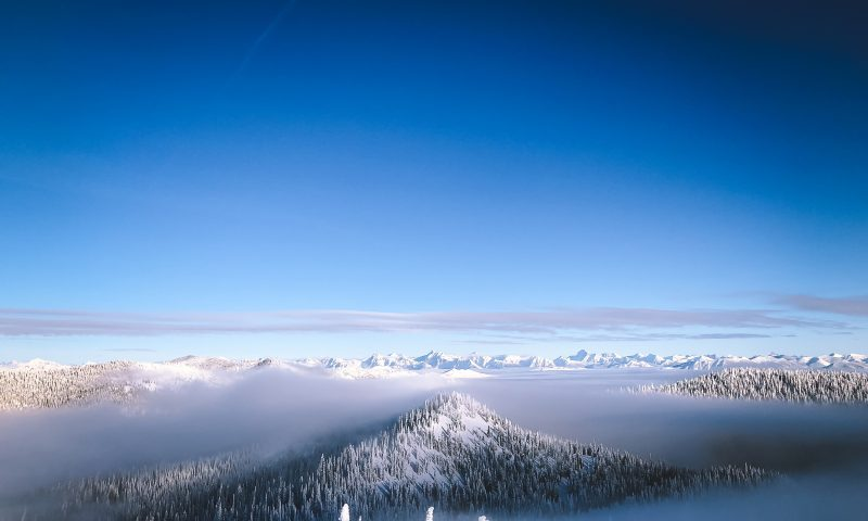 Scenic image of mountains and forests covered in snow, with blue to dark blue sky above.