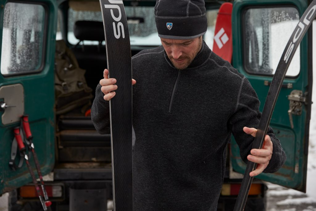 A man dressed in KUHL clothing prepares skis for skijoring.
