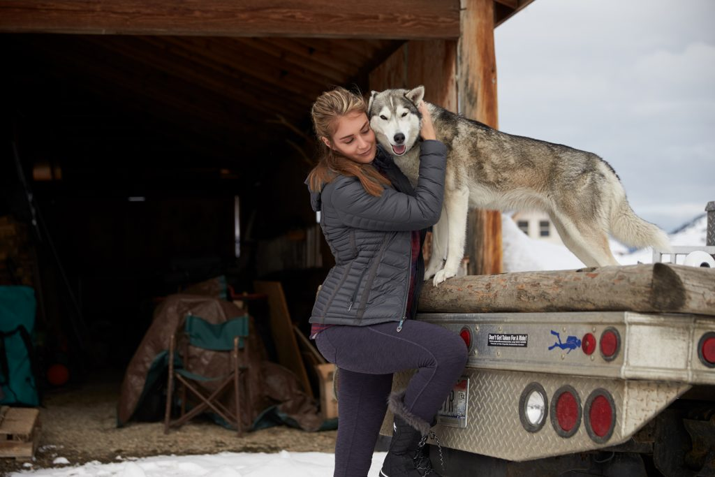 A woman hugging a dog on a truck.
