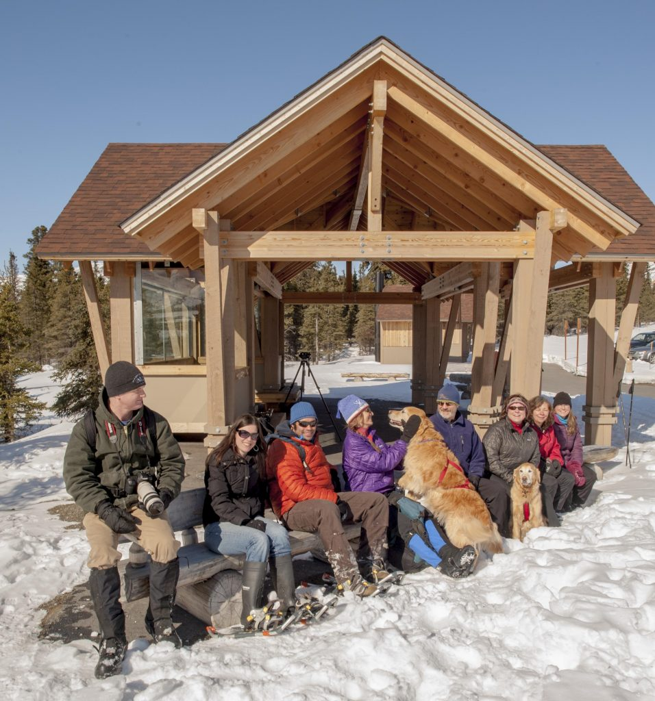 A group of skijoring enthusiasts resting next to a wooden cabin in the snow.