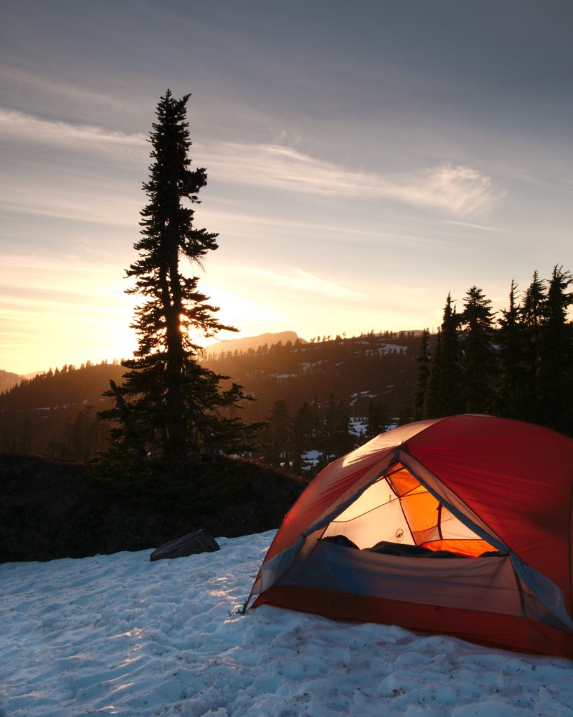 An orange dome tent near trees during sunrise