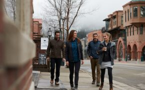 People dressed in KUHL clothing walk down the street in winter.