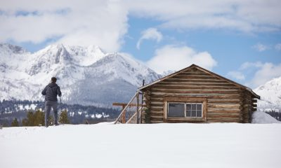 The Magic of Snow: A man standing on a snow next to a wooden cabin, overlooking a mountain