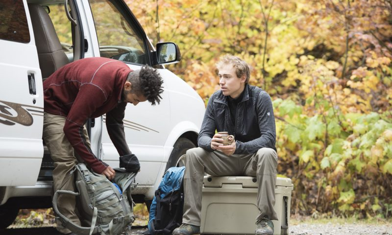 Two men preparing for a hike in a van, one is adjusting his backpack and the other is sitting on a box.