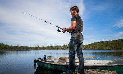 Young adult casting a line in a lake in KUHL clothing.