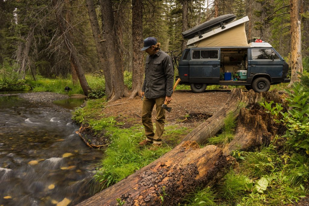 Bearanoid article image - Man in KUHL clothing standing near a creek with a van in the back.