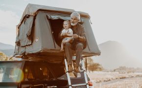 An older man holding a baby in a tent - KUHL clothing