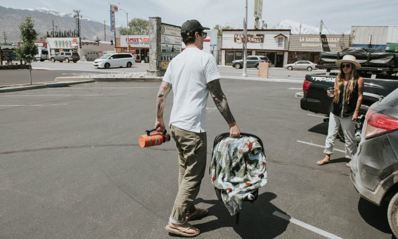 Dads Passion for Desert Hikes - Dad carrying a baby on a parking lot