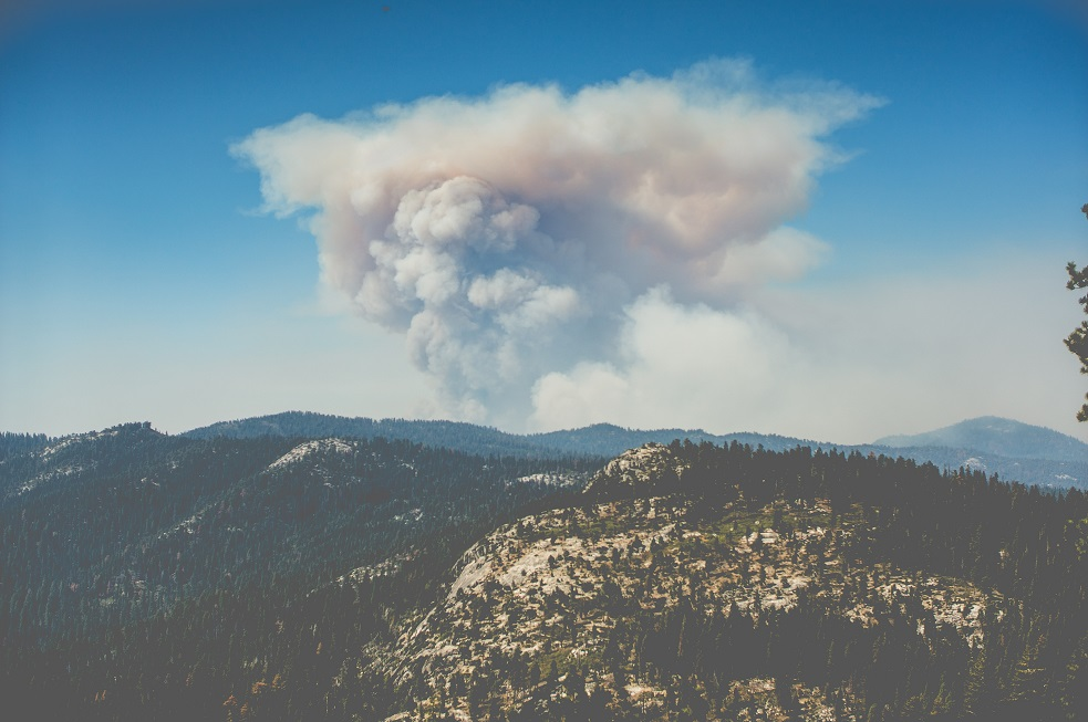 Guide to Wildfire Season - A mountainside with wildfire smoke in the distance.
