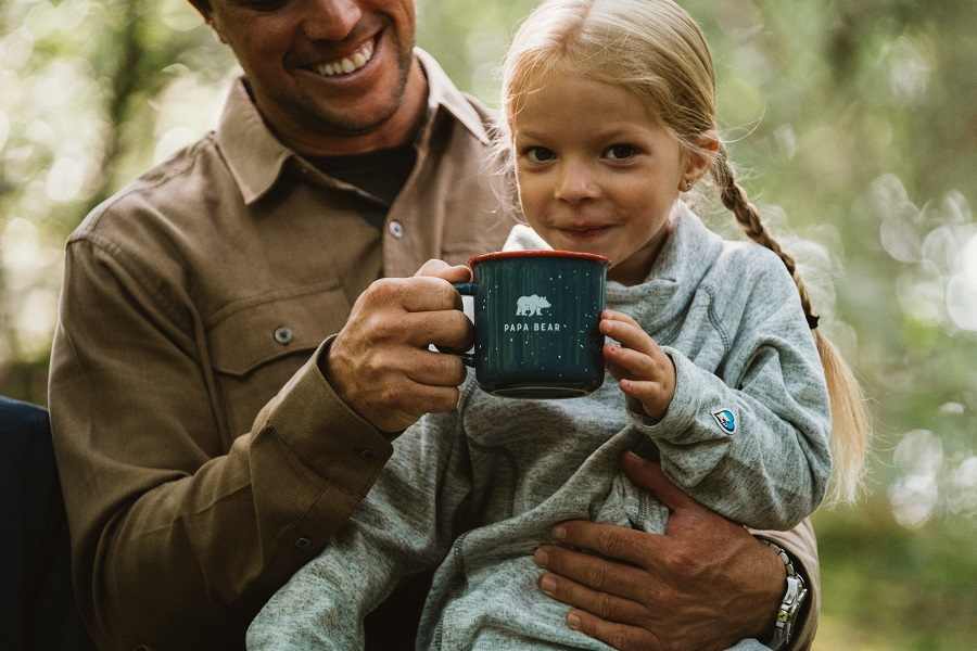 Have We Domesticated the Wild Child - A girl sitting in her father's lap, drinking from a cup.