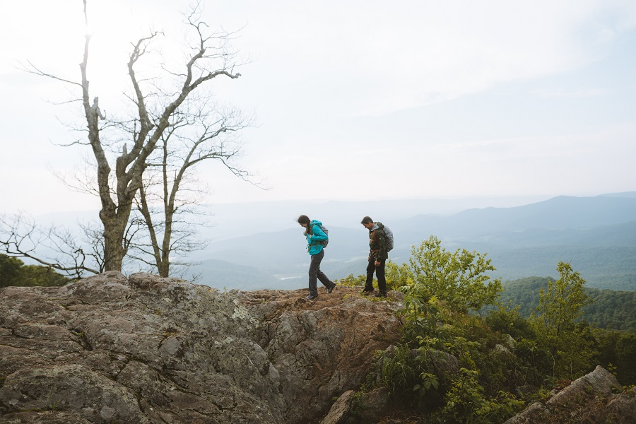 Indoorsy Partner to Outdoor Adventures - A woman and a man hiking in KUHL clothing on a rocky area.