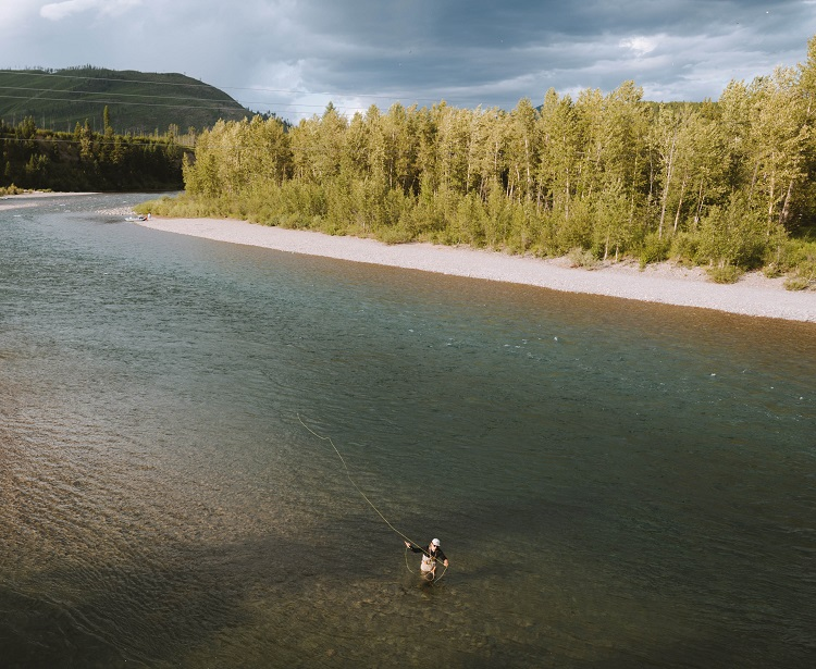 6 Ways to Salvage Your Summer - A man standing in the shallows fly fishing during day.