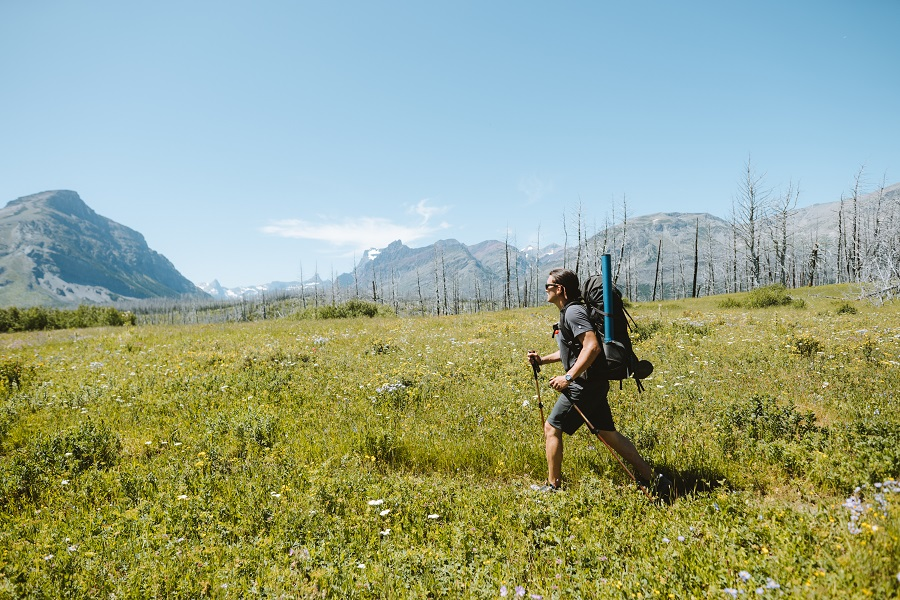 Choose Your Adventure - A woman hiking in KUHL clothes on a green field, sunny day.