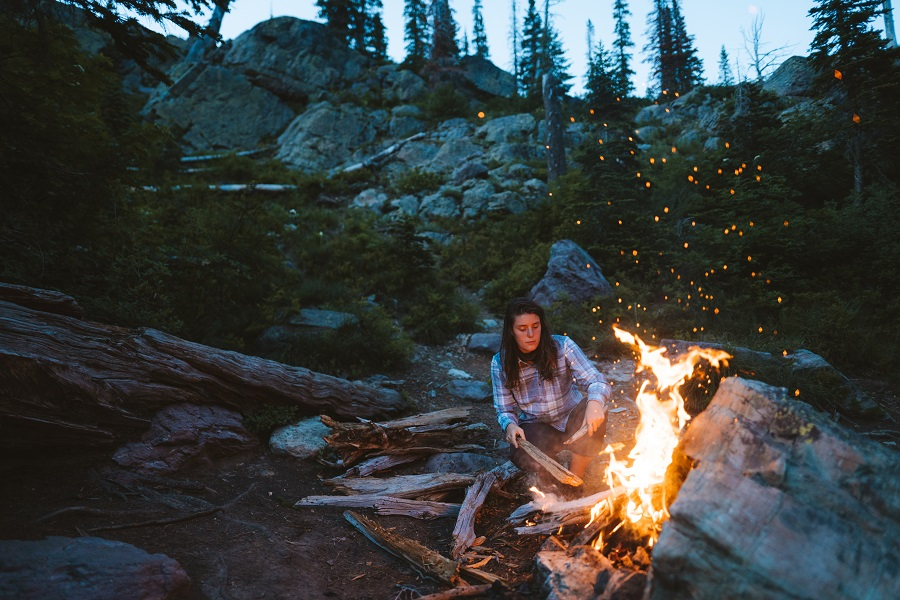 How to Survive Until Help Arrives - A woman in KUHL clothing crouching next to a campfire in the wilderness.