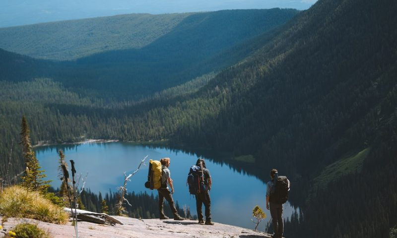 How to Survive Until Help Arrives - Hikers overlooking a lake in the distance, wearing KUHL clothing.