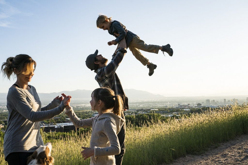 5 Ultimate Adventure Families - A family wearing KUHL clothing, and a dad playing with kids