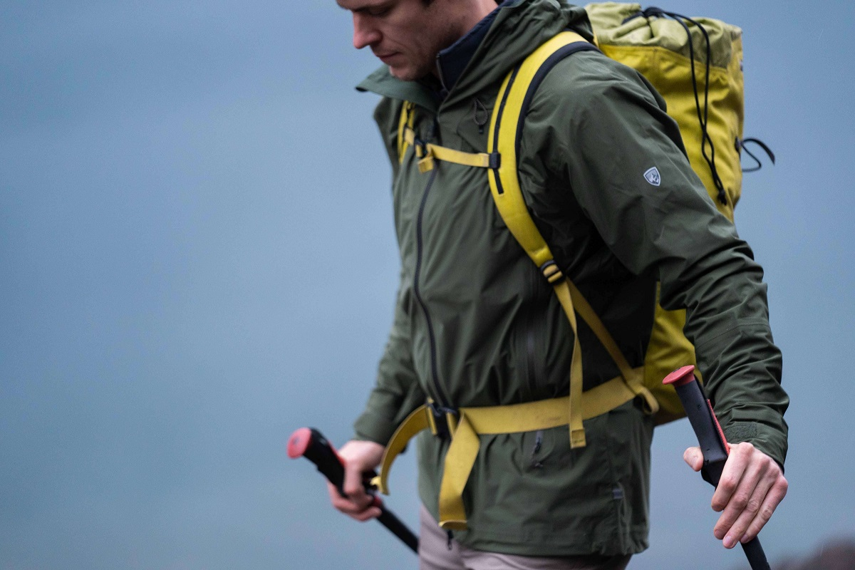 a man with shell jacket, yellow backpack and trekking poles