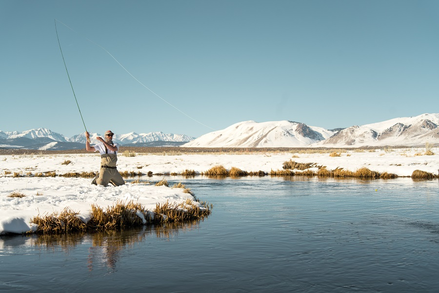 Man fishing with mountains in the background