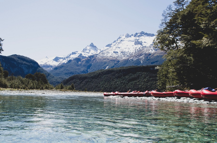 Red rafting boats in front of the snowy mountain