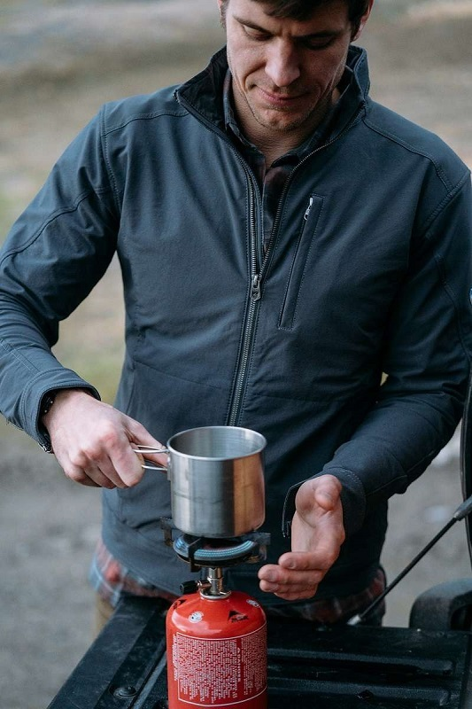 man cooking on a camp stove