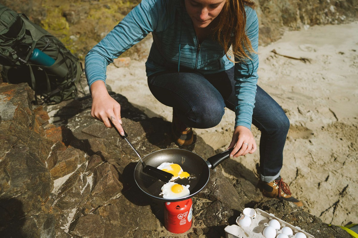 woman frying eggs outdoors in a pan