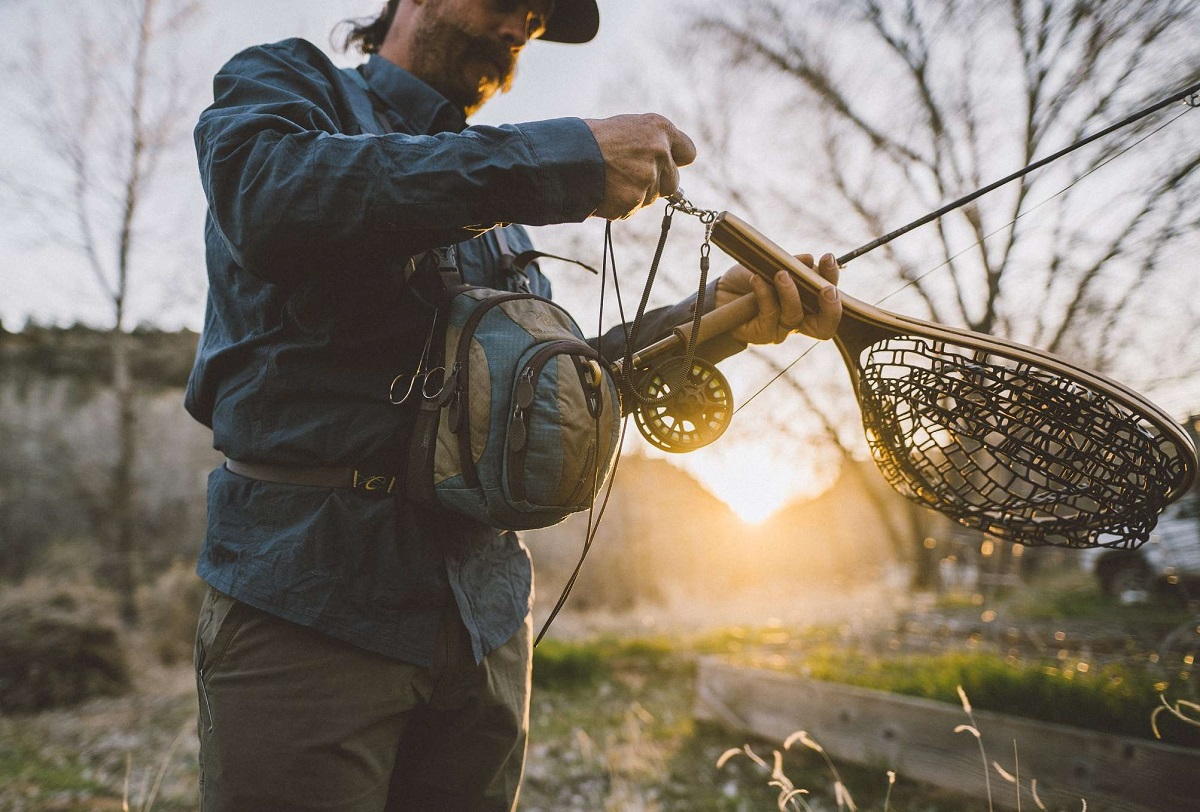 man holding a fishing rod and landing net