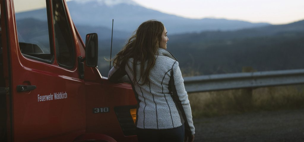 A woman leaning on a red truck wearing KUHL women's merino wool clothing