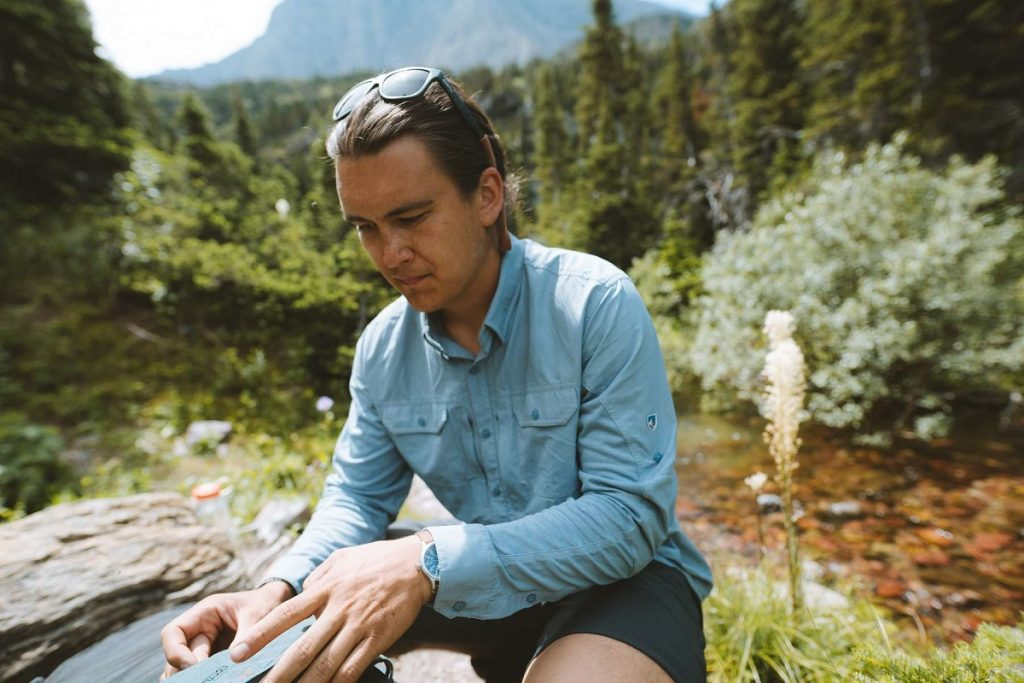 man in a blue shirt sitting in the outdoors