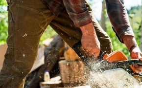 man in brown pants cutting wood with motor saw